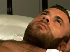 Hairy muscle bear Gianluigi poses on the bed and strokes his uncut cock