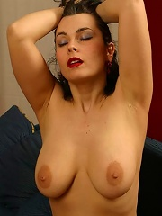 Busty mature brunette spreads her stockinged legs