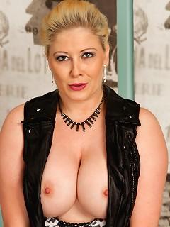 Big breasted mom in heels and stockings masturbates on sofa